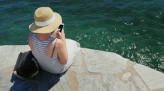 Woman sitting on the beach: Use a smartphone. The camera is tilt from the woman Stock Footage