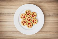 Seven round biscuits smiling faces on the white plate, humorous food - stock photo