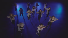 Dance performance of female group on a stage with blue lights and smoke - stock footage