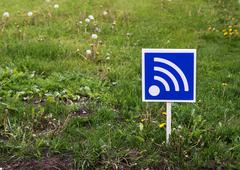 RSS sign on a green lawn. Free wifi simbol - stock photo