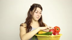 Young woman holding a basket, gets out of the basket head of garlic and assesses Stock Footage