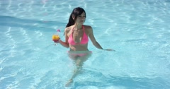 Young woman cooling off in a swimming pool Stock Footage