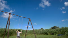 A young woman is swinging on a swing at a green field Stock Footage