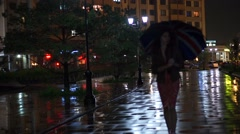 Girl with Union Jack umbrella walking at rainy night, slow motion video Stock Footage