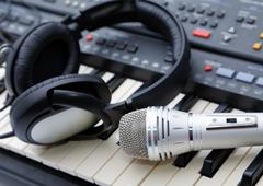 microphone and ear-phones lie on the keyboard - stock photo