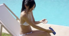 Young woman applying sunscreen Stock Footage