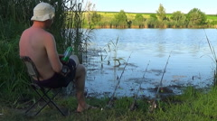 Man sitting in a folding chair on the bank of a large river. Stock Footage