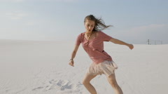 Young woman dancing hip-hop on sand at desert in summer day - stock footage