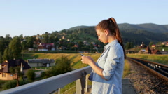 Smiling beautiful young woman with smartphone in mountains Stock Footage
