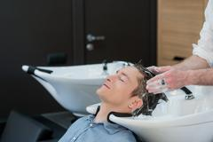 Close-up of a young man having his hair washed in hairdressing salon - stock photo