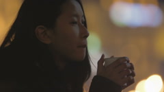 Young lonely Asian woman standing on the street and drinking hot tea, sadness Stock Footage