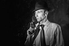 Handsome detective in hat holding a gun in the dark Stock Photos