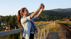 Smiling beautiful young woman taking pictures with smartphone in mountains Stock Footage