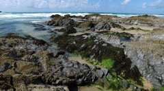 Gentle side-ward pan over rocks and seaweed, with distant headland and horizon. Stock Footage