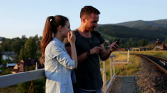 Smiling beautiful young couple taking pictures with smartphone in mountains Stock Footage