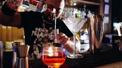 Bartender with piercings and dreadlocks making cocktail: pouring vodka Stock Footage