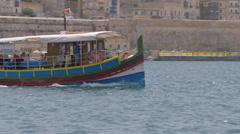 A Maltese traditional boat called Luzzu taking tourists around Valletta Malta Stock Footage