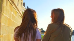 Two girl talking and walking next to the river Stock Footage