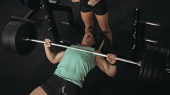 The man pumps his muscles with the help of the bar  at the gym Stock Footage