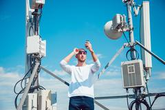 Man talking on the phone  the roof. Mobile antenna. Sky - stock photo