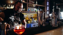 Bartender with piercings and dreadlocks putting ice into glass Stock Footage