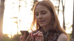 Girl laughing while using mobile phone in countryside Stock Footage