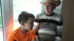Grandfather and grandson talking, laughing and looking at the camera - the old Arkistovideo