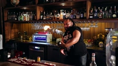 Charismatic bartender juggling bottle with fire and shaker - stock footage