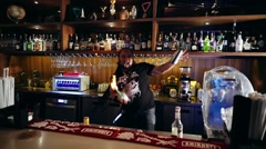 Bartender with piercings and dreadlocks juggling bottle with fire and shaker Stock Footage