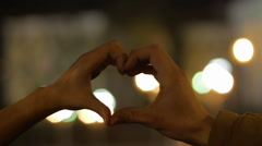 Happy boy and girl having fun, showing heart hand sign at camera, romantic date Stock Footage