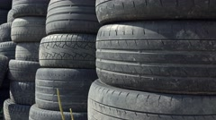 Stacks of old used car tyres 4K zoom in shot. Disposal site Stock Footage