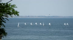 Small yacht under sail floating in the sea On the horizon is visible city Stock Footage
