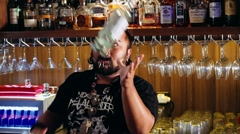 Artistic bartender with piercings + dreadlocks juggling bottle torch and shaker Stock Footage