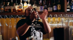 Charismatic bartender juggling bottle torch and shaker - stock footage