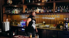 Charismatic bartender with piercings and dreadlocks practices juggling bottle - stock footage
