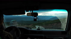 Young man drives a car in mountains. Travel and adventure concept. Toned picture Stock Footage