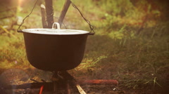 Camping scene: a pot with food being prepared hangs over the bonfire Stock Footage