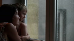 Mother and son awaiting someone to come looking out the window during the rain Stock Footage