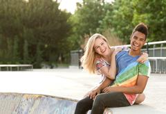 Happy and joyful people hanging around in a skate park. Stock Photos