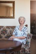 Elderly woman sitting on a couch at old age home Stock Photos