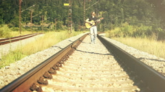 Sepia toned footage of a young man walking along the railway playing guitar Stock Footage