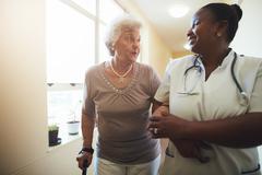 Nurse assisting senior female patient to walk Stock Photos