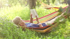 A boy rocks lying in the hammock and reads a book Stock Footage