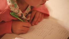 Little girl is doing her homework - stock footage