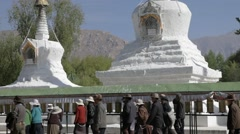 People in Tibet going past two stupas. Stupa in Potala place Stock Footage
