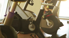 A man works out on an exercise bike late in the afternoon Stock Footage