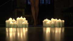 Elegant woman bare legs goes forward between burning candles in dark room Stock Footage