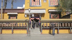 China, Tibet, Lhasa. Spinning prayer wheels near tibetian building - stock footage