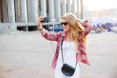 Young pretty woman taking a selfie at the square in the city - stock photo