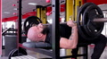 Strong muscular bodybuilder pushing heavy barbell, doing bench press exercise Footage